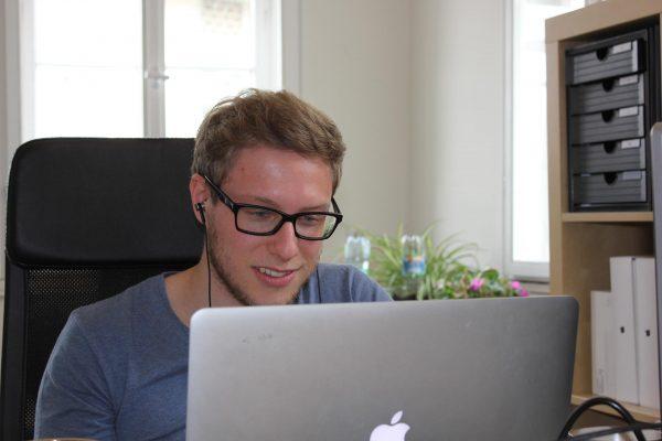 Mitarbeiter am Arbeitsplatz in Laptop schauend